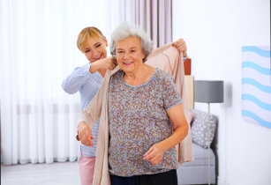 caregiver helping senior woman wear her blouse