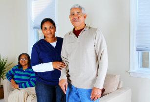 caregiver helping senior man stand up