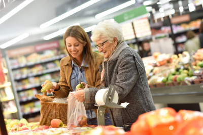senior woman going grocery shopping with her younger companion