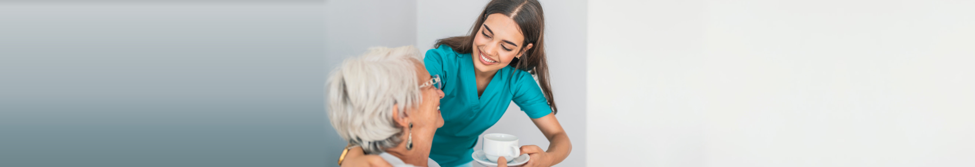 caregiver giving a cup of tea to a senior woman
