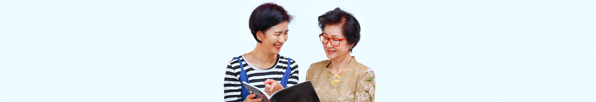 senior woman and caregiver reading a book